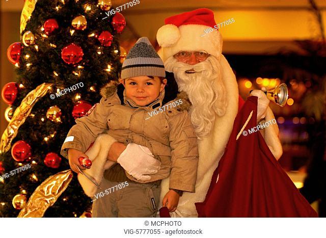 Germany, HAMBURG, 23.12.2006, Ein kleiner Junge mit dem Weihnachtsmann vor einem Tannenbaum, 2007 - Hamburg, Germany, 23/12/2006