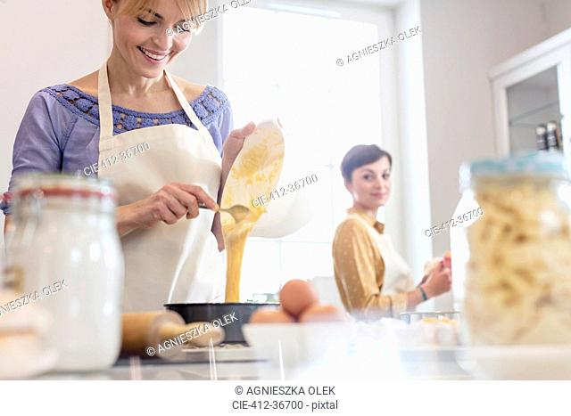 Female caterers baking, pouring cake batter into tin in kitchen