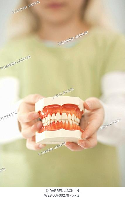 Germany, Bavaria, Landsberg, Girl 8-9 holding model of teeth
