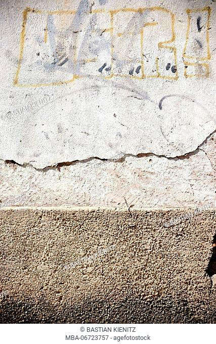 Close-up of cracked plaster layers on the surface of a wall