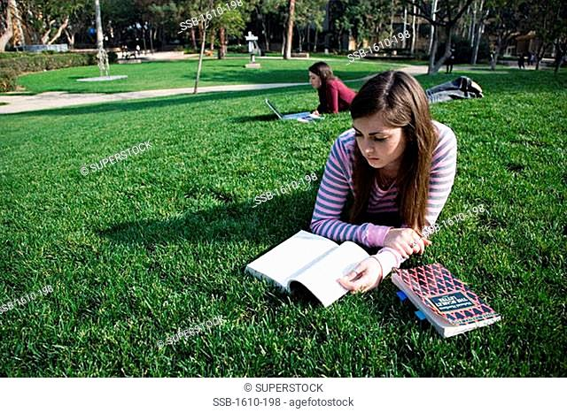 Close-up of a young woman reading a textbook on a lawn