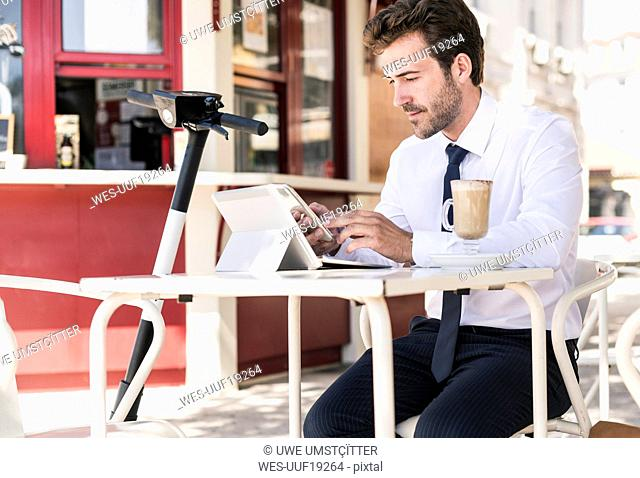 Young businessman using tablet and mobile phone at a cafe in the city, Lisbon, Portugal
