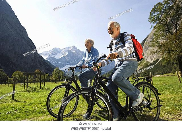 Mature Couple Cycling Along Path Stock Photos And Images