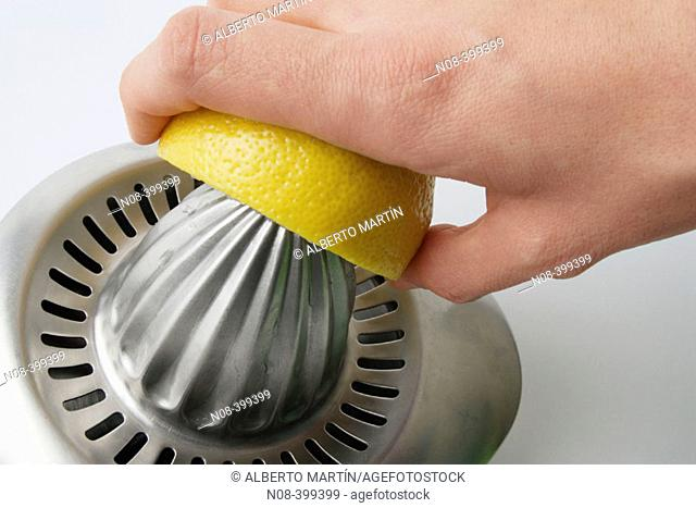 Hand squeezing lemon on metallic squeezer