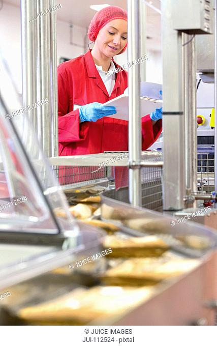 Worker with clipboard at production line in cheese processing plant