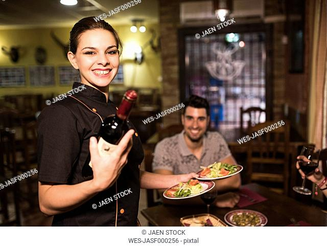 Portrait of smiling waitress serving wine and dishes