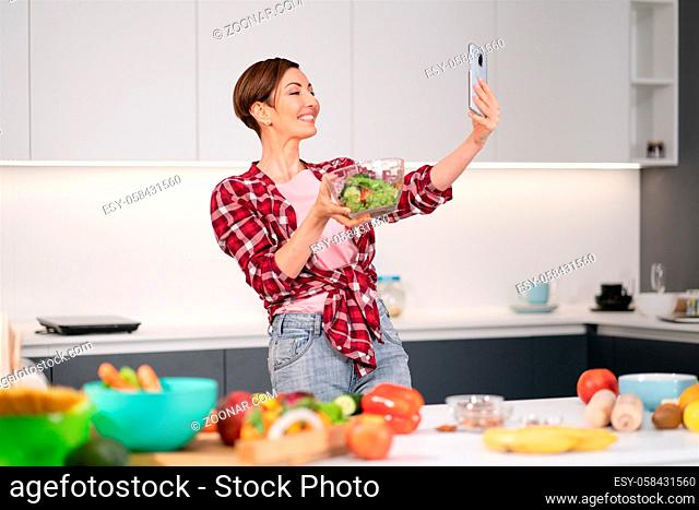 Pretty woman happy taking selfie using her smartphone while cooking fresh salad wearing a plaid shirt with a bob hair style