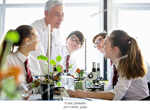 Teacher talking to high school students conducting scientific experiment in biology class