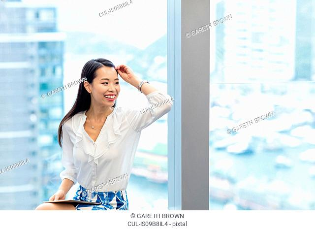 Woman with digital tablet sitting on windowsill looking away smiling