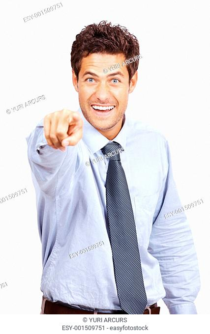 Portrait of an excited young male business executive pointing at you against white background
