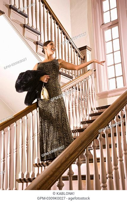 Hispanic woman in formal gown standing on stairs