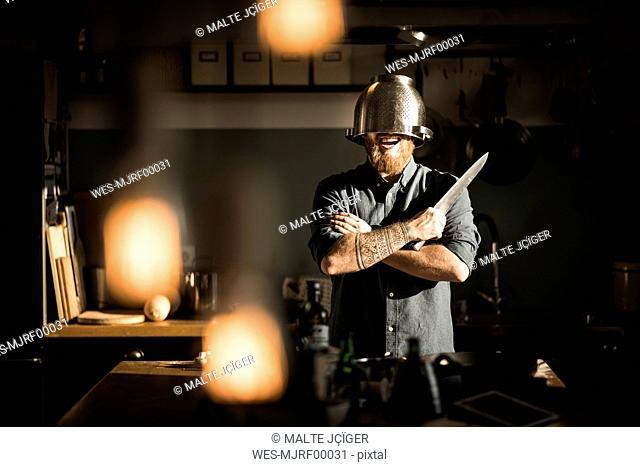 Man with kitchen knife standing in kitchen, wearing colander as helmet