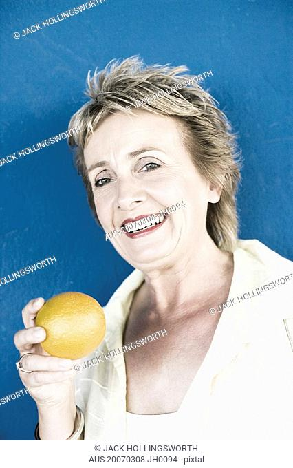 Close-up of a mature woman holding an orange and smiling