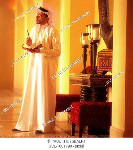 Arab man holding a filofax and a pen