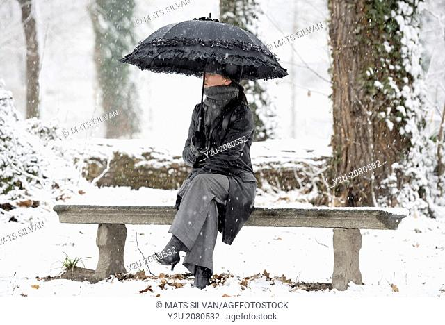 Elegant woman sitting on a bench with umbrella when it's snowing in locarno ticino switzerland