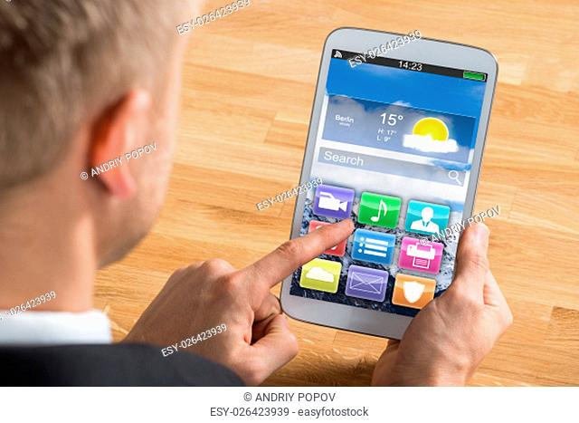 Close-up Of Young Businessman Using Digital Tablet With Multicolored App At Desk