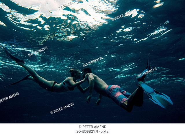 Underwater view of couple wearing flippers