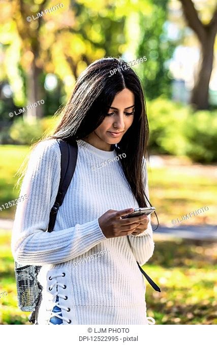 A young female student of Lebanese ethnicity checking her smart phone while walking in a university campus; Edmonton, Alberta, Canada