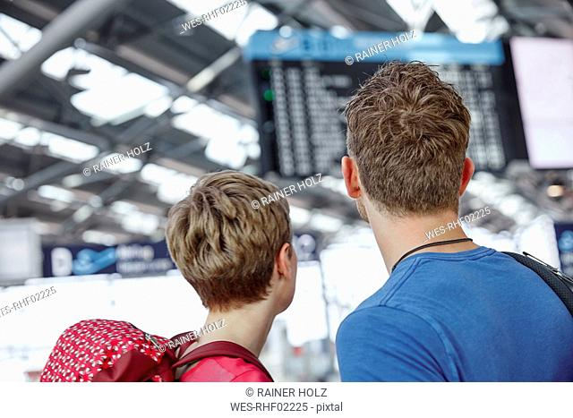 Rear view of couple looking at arrival departure board at the airport