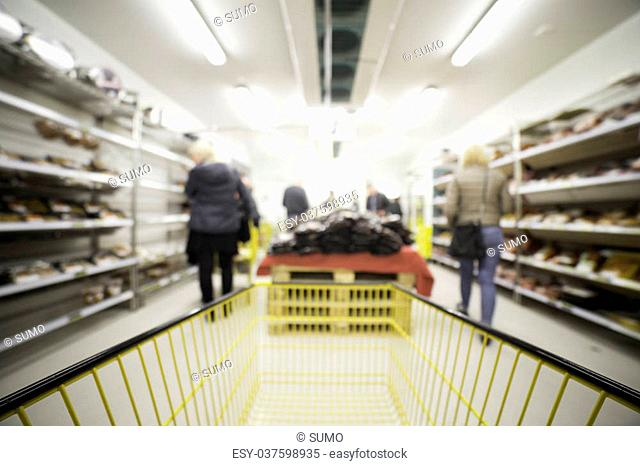 Out of focus shot of people shopping in a grocery store setting, shot from the shopping cart, great as a background in designs