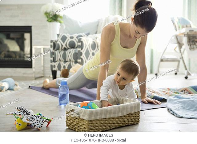 Mother doing yoga by baby girl at home