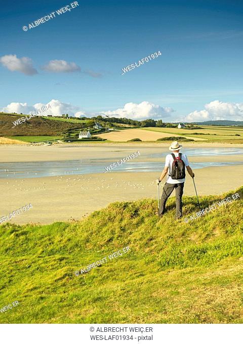 France, Bretagne, Active senior hiking on the beach of Treguer