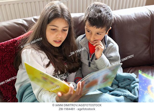 Older sister reading a story to her brother