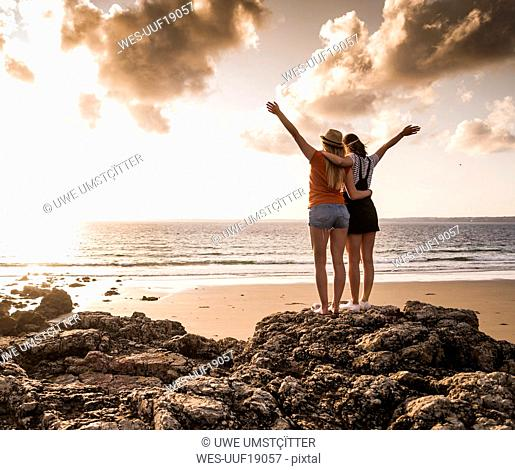 Two girlfriends standing on rocky beach, waving at sunset, rear view