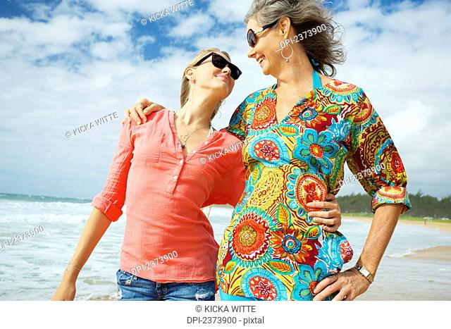 A mother and daughter together on the beach; Kauai, Hawaii, United States of America