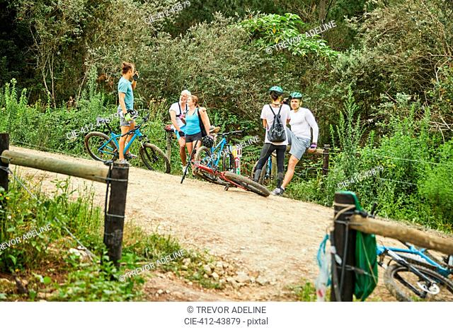 Friends mountain biking, resting on trail