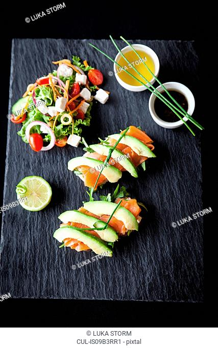 Smoked fish and avocado open sandwiches with salad and dipping sauces on slate, overhead view