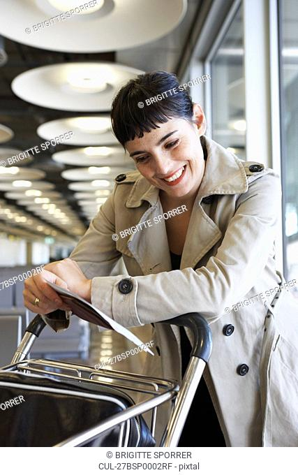 Woman at airport looking at ticket