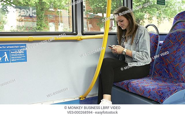 Young woman using mobile phone on bus,rushes to get off at stop but leaves phone on seat as camera zooms in.Shot on Sony FS700 in PAL format at a frame rate of...