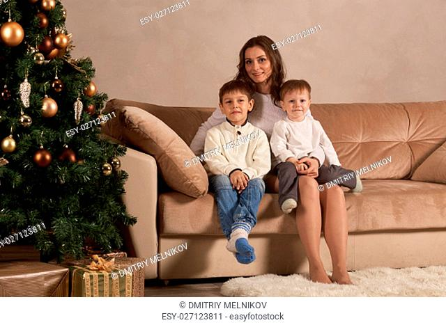 Happy family are sitting on a sofa near Christmas tree at home. Merry Christmas and Happy New Year. Beautiful young mother with two sons