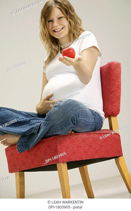 A pregnant woman holding apple
