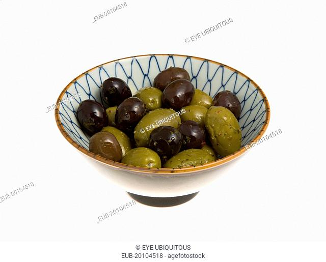 Ripe black and green olives Olea europaea in olive oil in a bowl against a white background