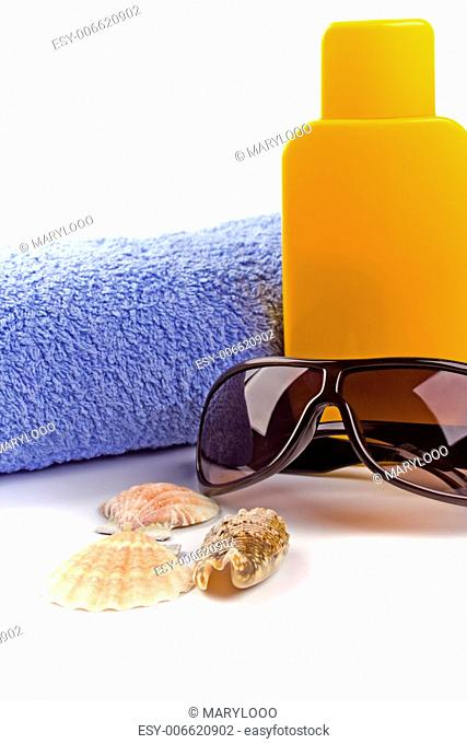 towel, sunglasses and lotion closeup on white background