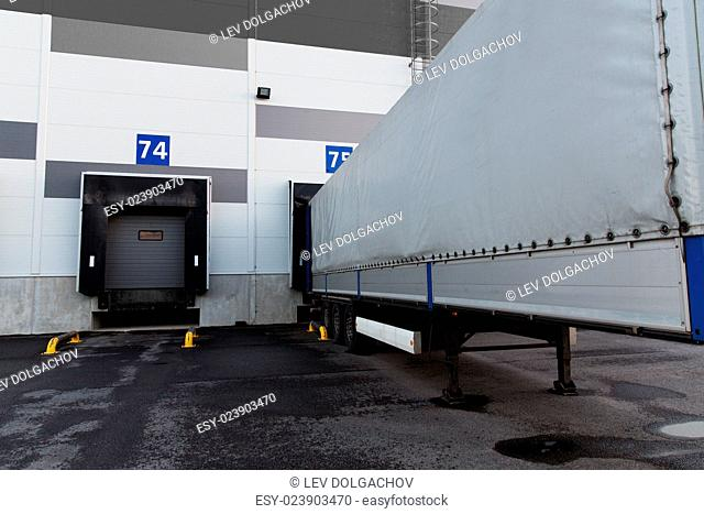logistic, storage, shipment, transportation and loading concept - warehouse gates and truck loading