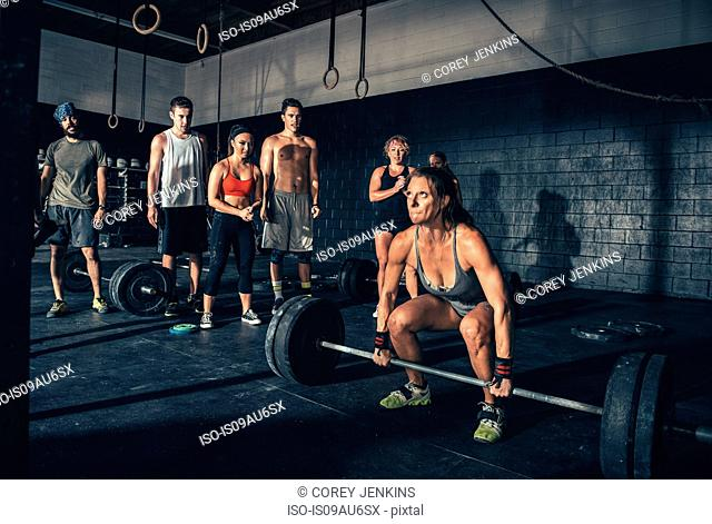 Woman performing barbell lift in gym