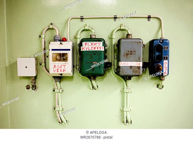 Fuse boxes on green wall