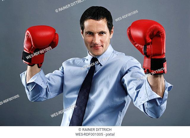 Portrait of mature man wearing boxing glove, smiling