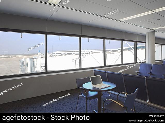 Business airport lounge, view outside and a laptop on a table