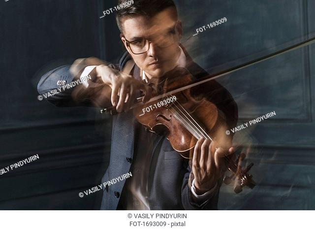 Blurred motion of confident violinist playing violin against wall