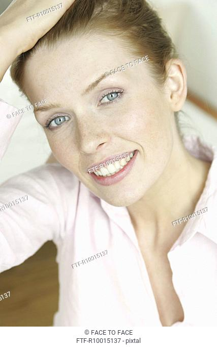 A blonde woman smiles as she looks at the camera