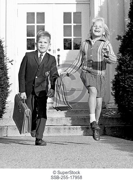 Boy and a girl running in front of a school