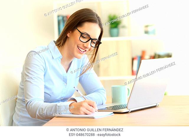 Happy woman wearing eyeglasses writing in a notebook on a table at home