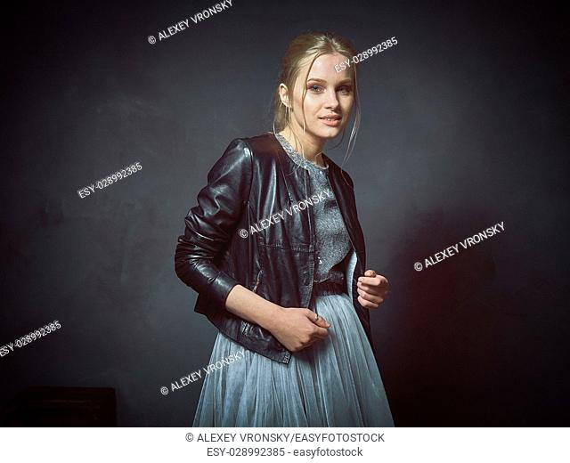 The girl dressed in various wedding outfits moving in front of the camera in the Studio