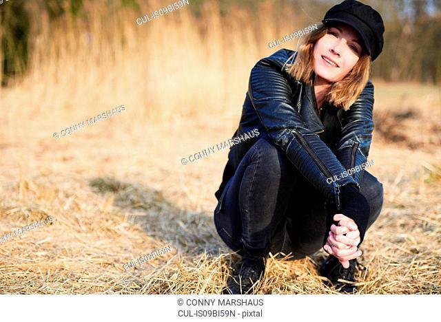 Cool woman wearing cap crouching on field straw, portrait
