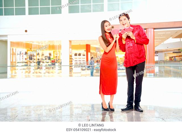 Asian Chinese couple in cheongsam dress holding red envelopes. Happy Chinese New Year