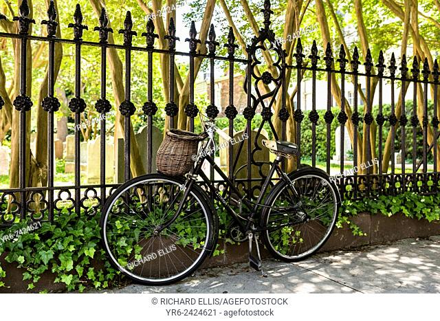 A vintage bicycle chained to the fence of the French Huguenot Church along Church Street in historic Charleston, SC